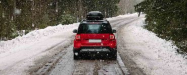A red car traveling down a snowy road in a mountainous region