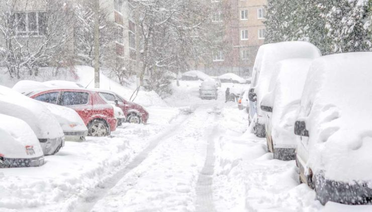 A parking lot, during a snowstorm, filled with cars that are covered in snow