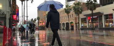 A man carrying an umbrella past the Chinese Theater in LA
