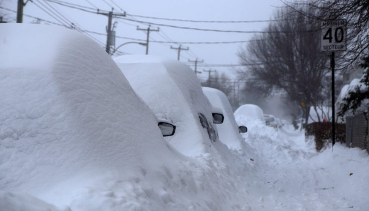 Vehicles hidden by mounds of snow