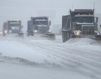 Snow being cleared from highway by massive plow trucks