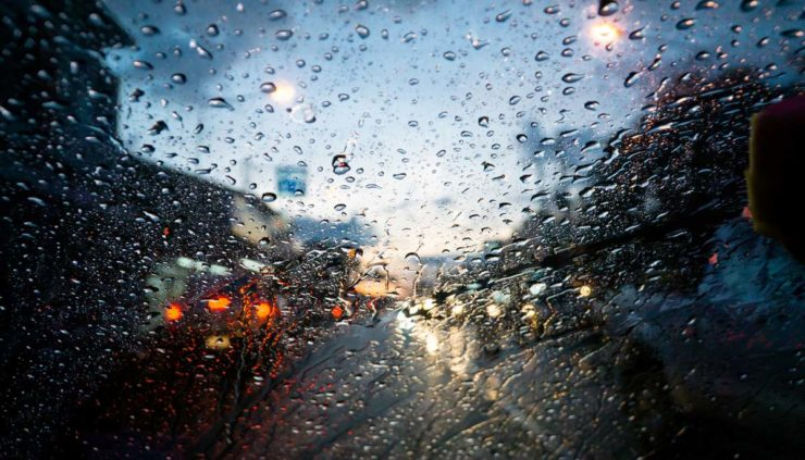 a driver looking through a rainy windshield at cars stopped in traffic
