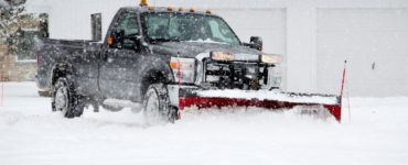 a large black pickup truck with a snow plow attached to it pushing snow