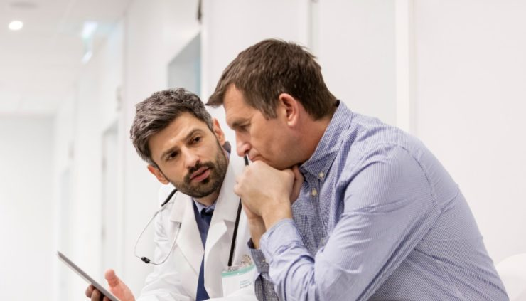 a man looking at test results and speaking with his doctor, both looking serious