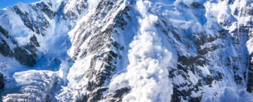 a snow avalanche on the side of a wintery mountain