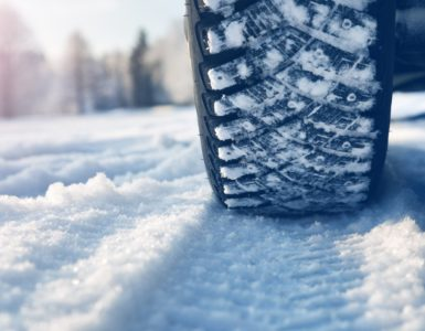 tires driving on a snowy road, leaving tread marks