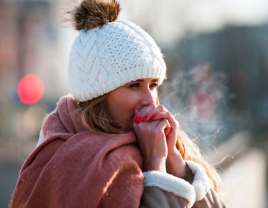woman wearing a big scarf and hat blowing on her hands to keep warm on a cold, clear day