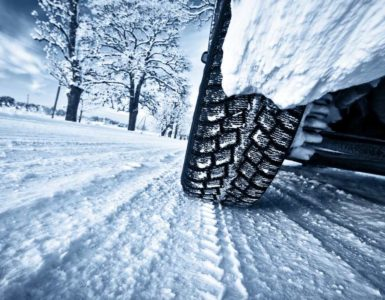 a close up of car tires on a wintery, snowy road