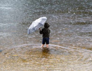 a little boy holding an umbrella and wading into water in the rain