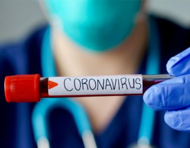 a nurse wearing a face mask and holding a vial of blood that reads coronavirus