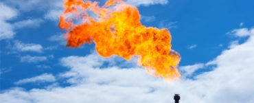 methane gas burning off of a pipe in the air