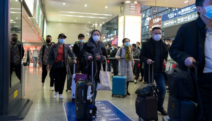 people wearing face masks to protect from the coronavirus walking through an airport