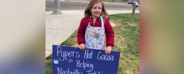 pyper holding a sign about her hot chocolate stand