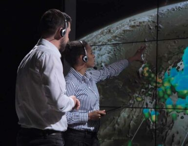Meteorologists track a hurricane on a large display