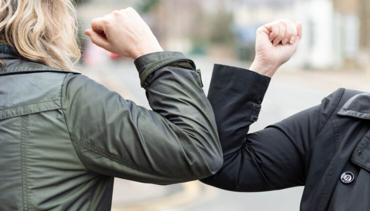 Two women greet with an elbow bump as part of Social Distancing