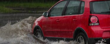 a small red car driving on a heavily flooded road
