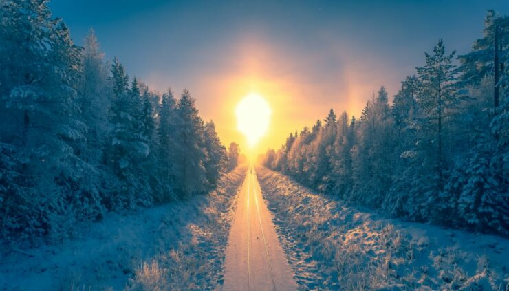 the sun rising over a snow covered road in the forest