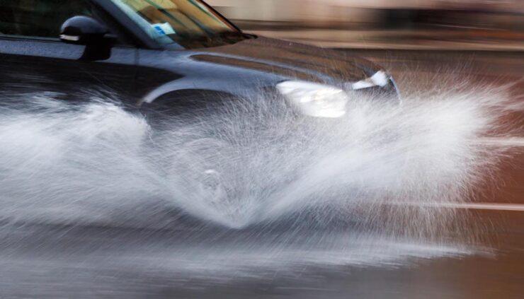 a car drives through heavy rain