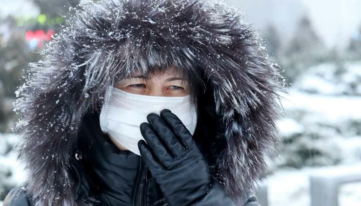 a sick woman in a medical mask wearing a heavy coat in the snow