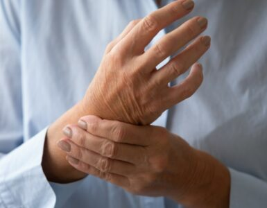 a woman rubbing her hands due to pain from arthritis