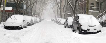 a Manhattan city street covered in snow during a noreaster