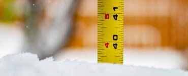 a ruler is being used to measure snow