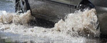 car driving through flood waters