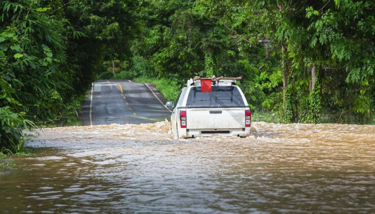 A truck driving through a flooded out road