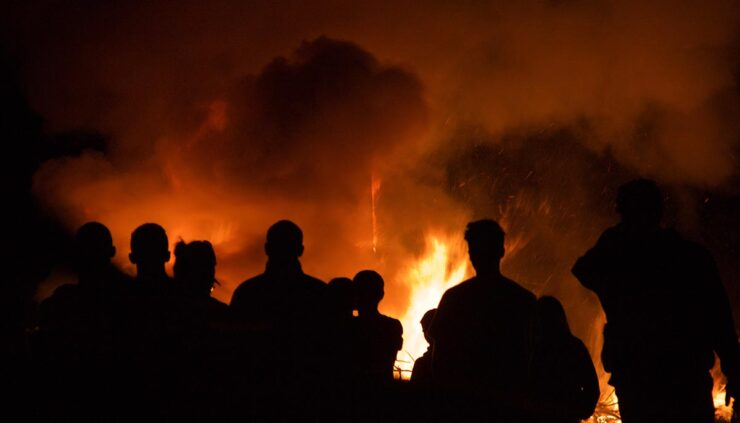 silhouettes of people near fire