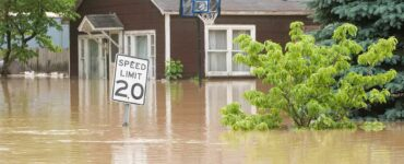 a flooded house with a speed limit sign