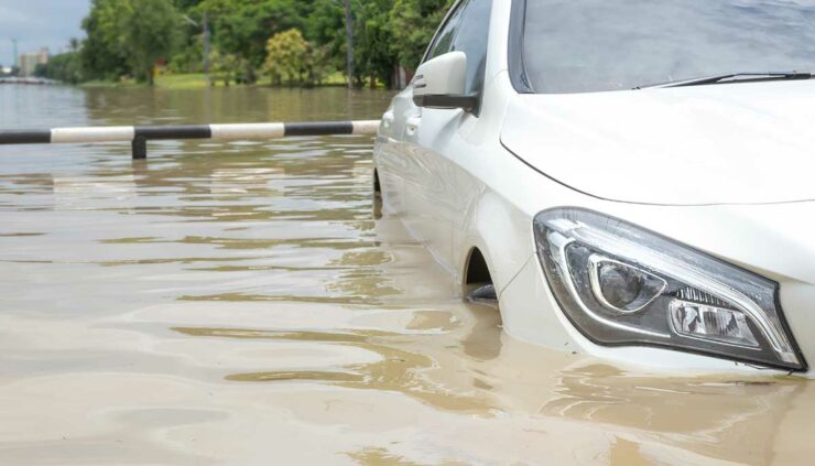 white car stranded on a flooded road