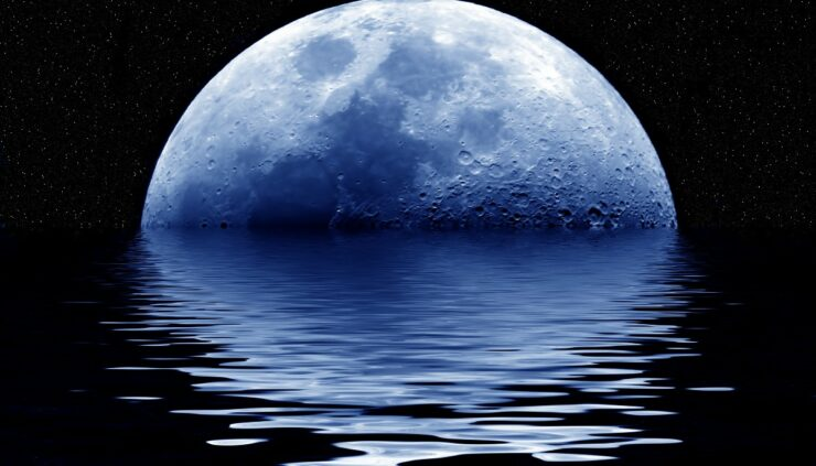a blue moon rising over a body of water