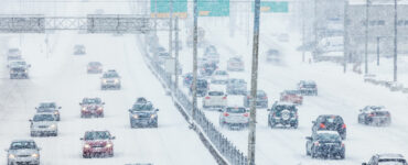 cars driving on highway during snowstorm