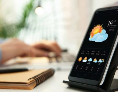 weather forecast displayed on smartphone, sitting on desk