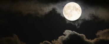 full moon surrounded by clouds in night sky