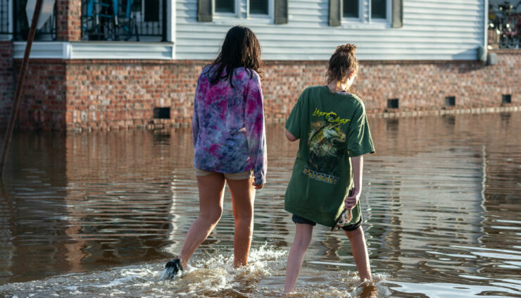 two girls walking in water after Hurricane Laura