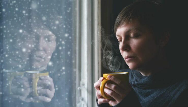 woman drinking coffee by the window