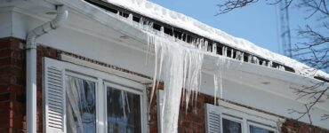 home in winter, gutters full, ice bending gutters