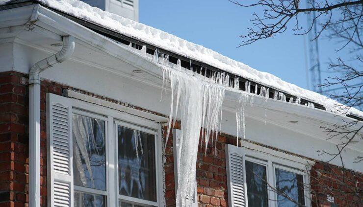 home in winter, gutters full, ice bending gutters