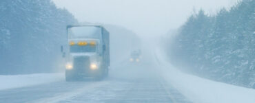 trucks driving on snowy highway with limited visibility