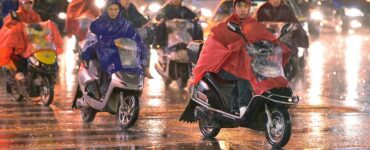 scooters crossing the street in the rain in China