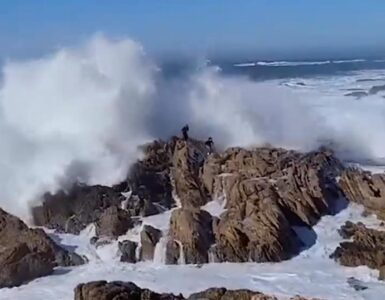 people avoid crashing waves on rocks