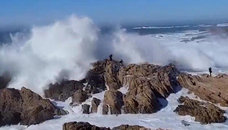 people avoid crashing waves on rocks