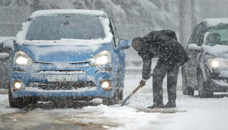 man shovels snow around car