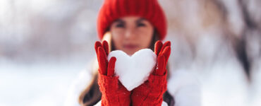 Woman holding a snowball shaped like a heart