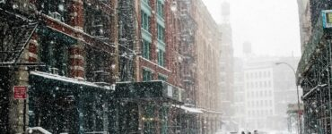 people walking through a snowstorm in a big city