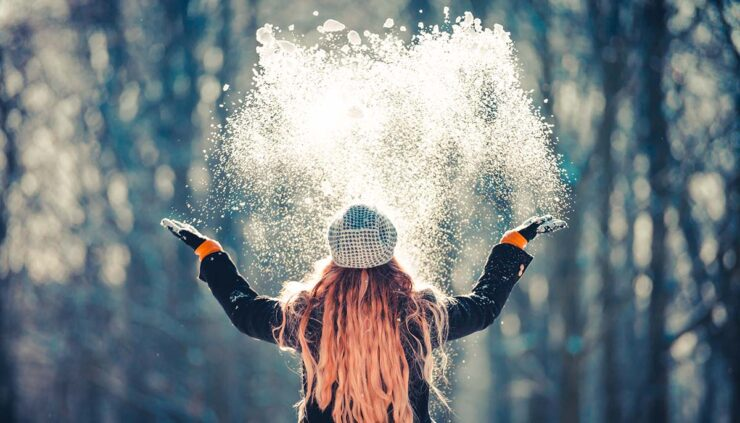 young woman throwing snow into the air