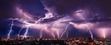 Multiple dramatic bolts of lightning over a city at night