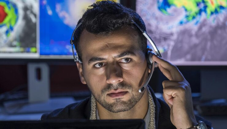 Meteorologist working at monitors