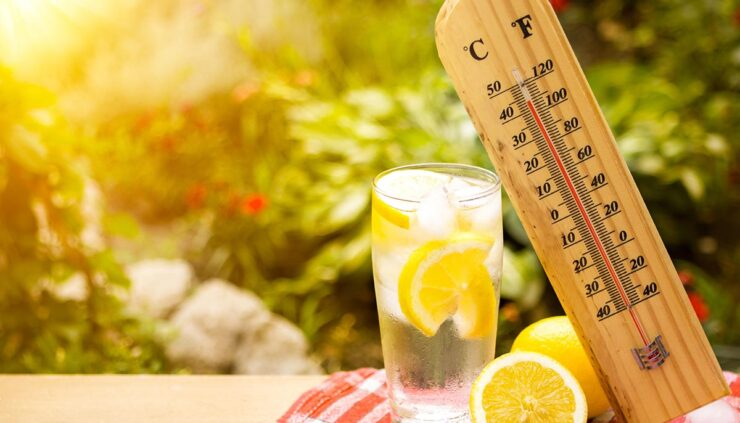 Thermometer and a glass of lemonade on a sunny day, representing the concept of a hot summer day